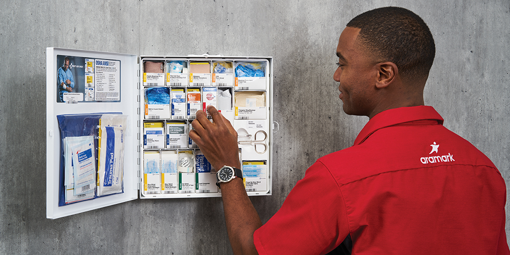 First aid supplier maintaining first aid supplies in cabinet.